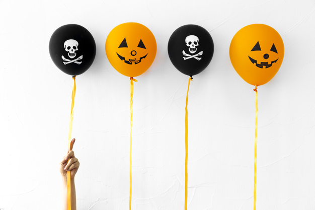 Crop hand with cute Halloween balloons