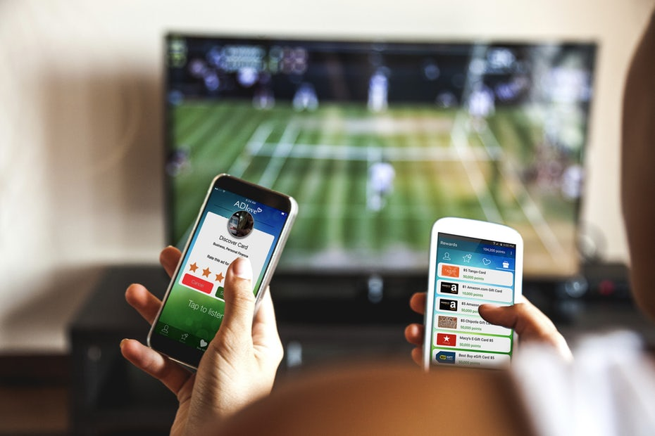 """Пара сидит на диване, смартфоны в руке, используя приложение во время просмотра спортивных """"width ="""" 4200 """"height ="""" 2800"""