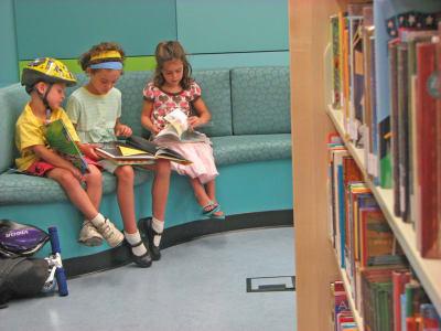 Трое детей сидят и читают книги индивидуально