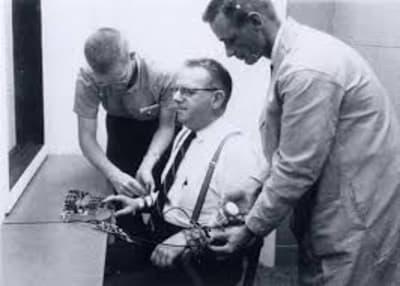 Черно-белая фотография двух исследователей, прикрепляющих шоковые датчики к участнику исследования