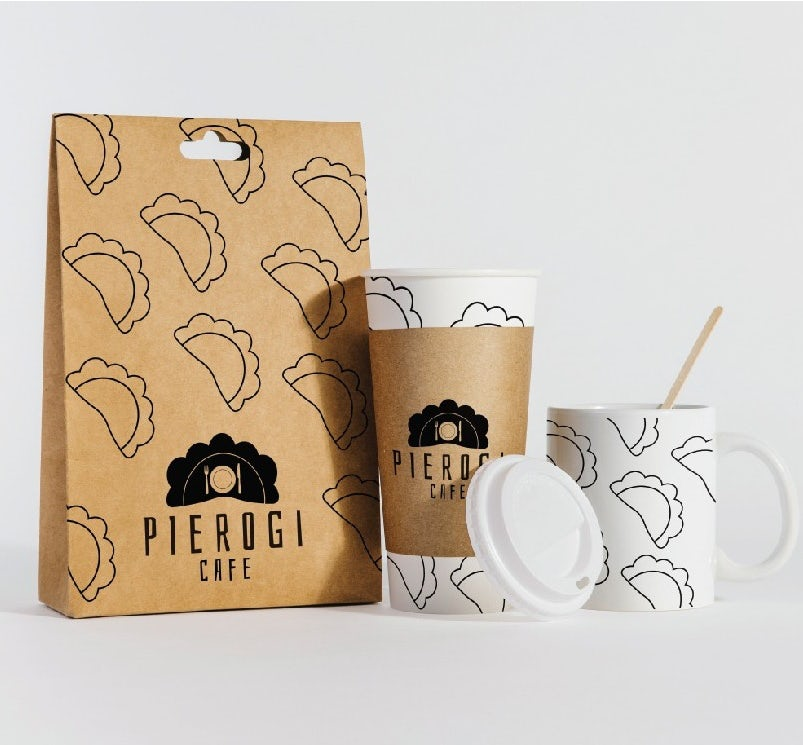 коричневый бумажный пакет с линейными иллюстрациями вареников рядом с бумажной кофейной чашкой и кружкой