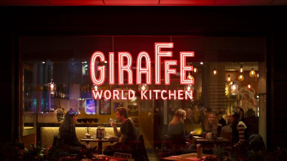 """стеклянное окно с видом на ресторан с большой вывеской Giraffe World Kitchen в красных неоновых огнях """"width ="""" 2048 """"height ="""" 1152"""