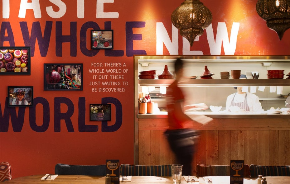 """внутренний вид кухонной стойки на фоне оранжевой стены, заполненной фотографиями """"width ="""" 2048 """"height ="""" 1301"""