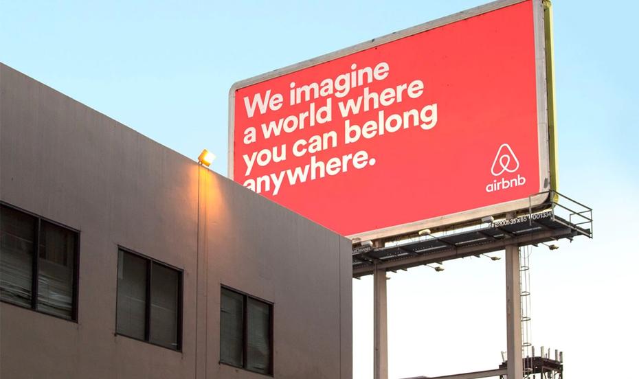"""Рекламный щит Airbnb кораллово-розового цвета и текст, который гласит: мы представляем мир, в котором вы можете принадлежать чему угодно. """"Width ="""" 1600 """"height ="""" 950"""