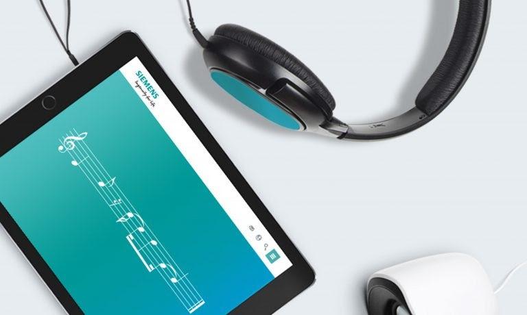 """планшет открыт с музыкальными нотами для аудиобрэнда Siemens на дисплее и черно-синими наушниками сбоку """"width ="""" 768 """"height ="""" 460"""