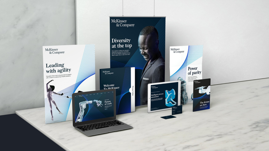 """a laptop, tablet, folders, brochures, and banners are displayed with the new brand design"""" width=""""2048"""" height=""""1153"""